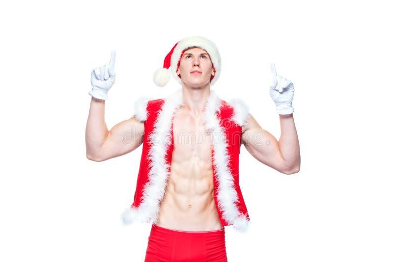 Sexy Santa Claus, die in weißes leeres Zeichen zeigt Der junge muskulöse Mann, der Santa Claus-Hut trägt, demonstrieren seine Mus lizenzfreie stockfotografie
