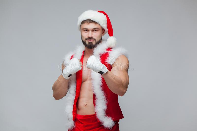 Christmas. Santa Claus . Young muscular man wearing Santa Claus hat demonstrate his muscles. Muscular Fighter royalty free stock photography