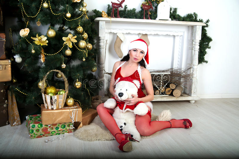 Santa Girl. Young beautiful girl lady woman model lover spectacular Snow Maiden. Light background Christmas, new year holiday presents teddy bear. Chic look stock photography