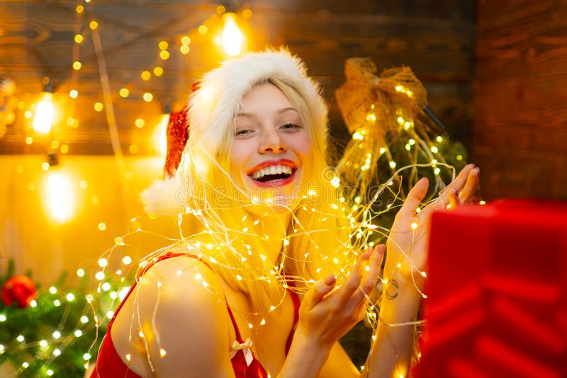 Sexy Santa woman posing on vintage wooden background. Night background with a sparkler. Christmas preparation - sensual stock photo