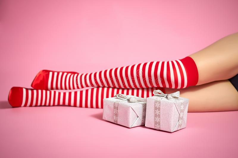 santa woman`s legs on a pink background and Christmas gifts stock image