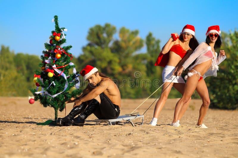 Sexy Santas  pulling Santa at the beach
