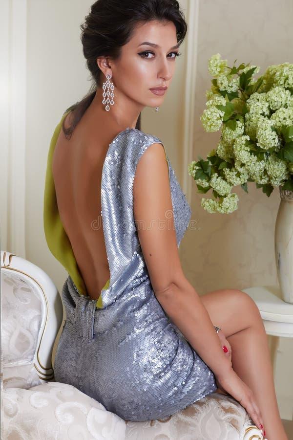 Sexy schöne junge Brunettefrau mit dem Abendmake-upchic gepflegt, ein kurzes Abendkleid tragend gestickt mit Silber lizenzfreie stockfotografie