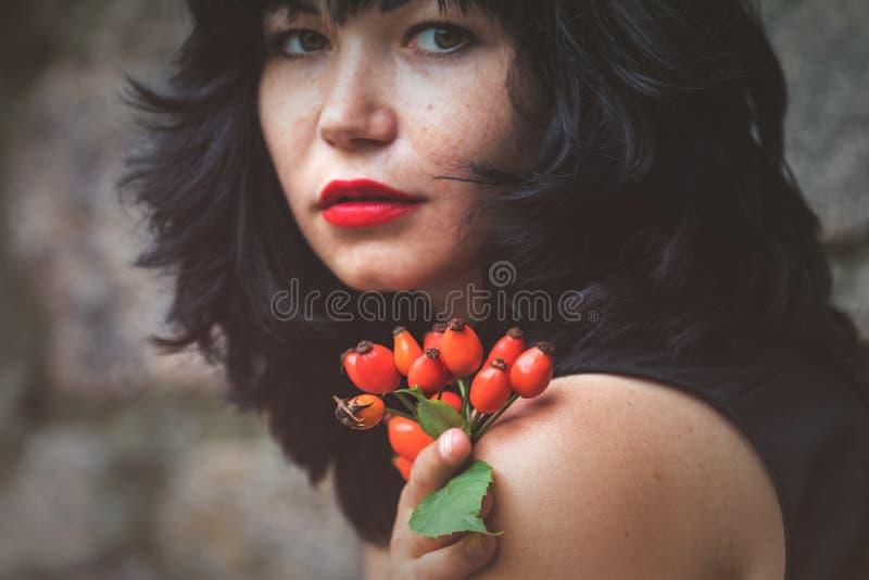 Sexy schöner hübscher Brunette mit rotem Lippenstift mit Rotrose h lizenzfreie stockbilder