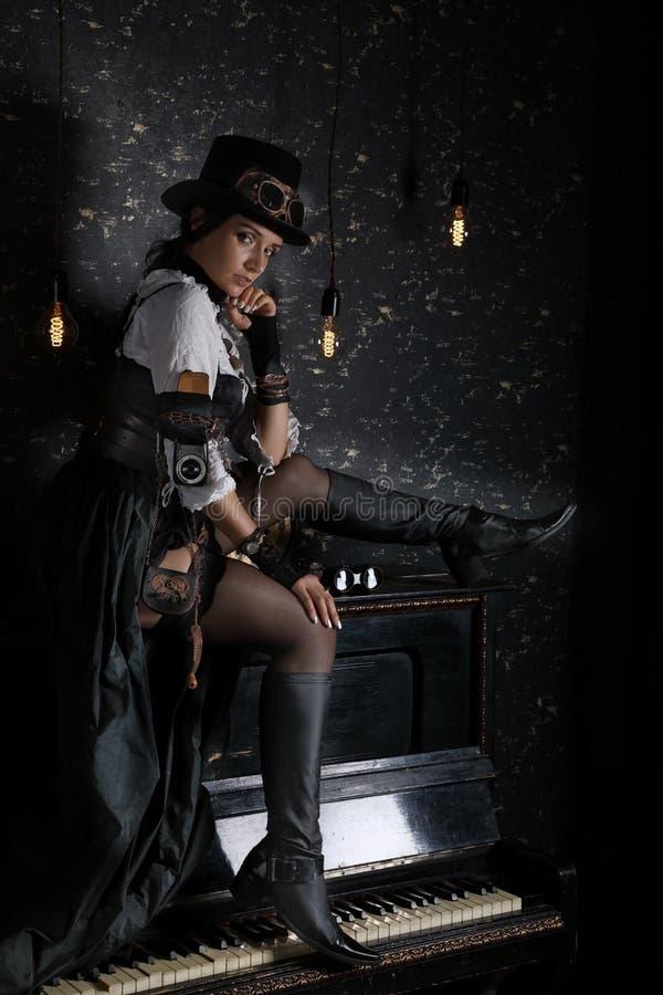 Sexy schönes Mädchen, das auf Klavier sitzt stockbilder
