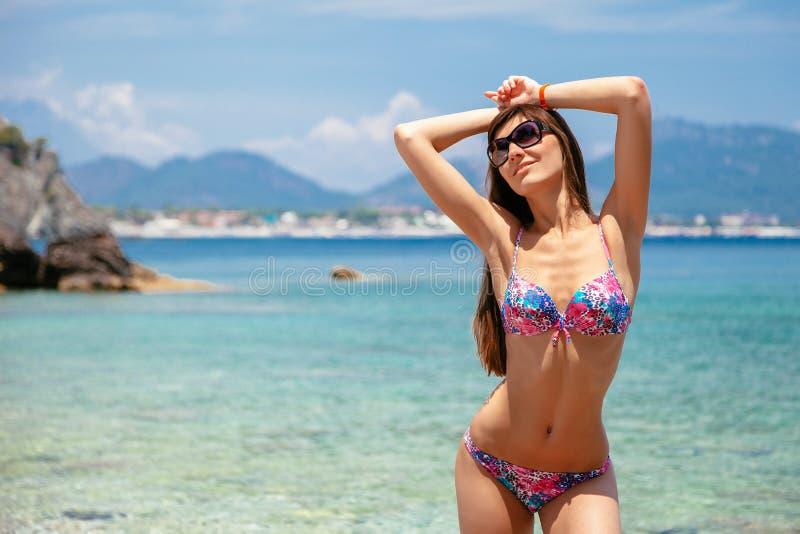 Sexy Schönheit im Bikini und in der Sonnenbrille auf Seehintergrund Seek?ste nahe Kemer, Antalya, die T?rkei stockbilder