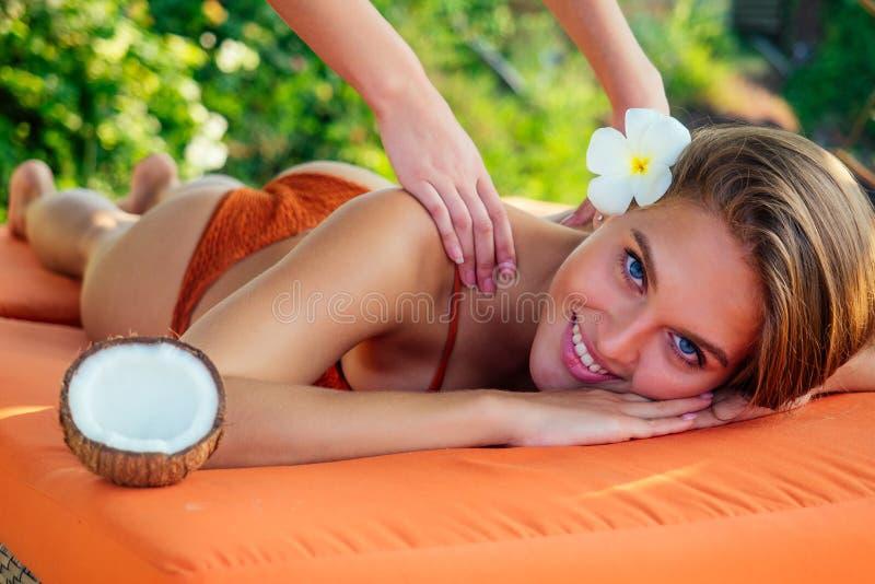 Sexy schneweißes Lächeln, perfekte Haut-Frau Plumeria Blume entspannende Massage am Strand Verwöhnmädchen im thailändischen Spa-S lizenzfreies stockfoto