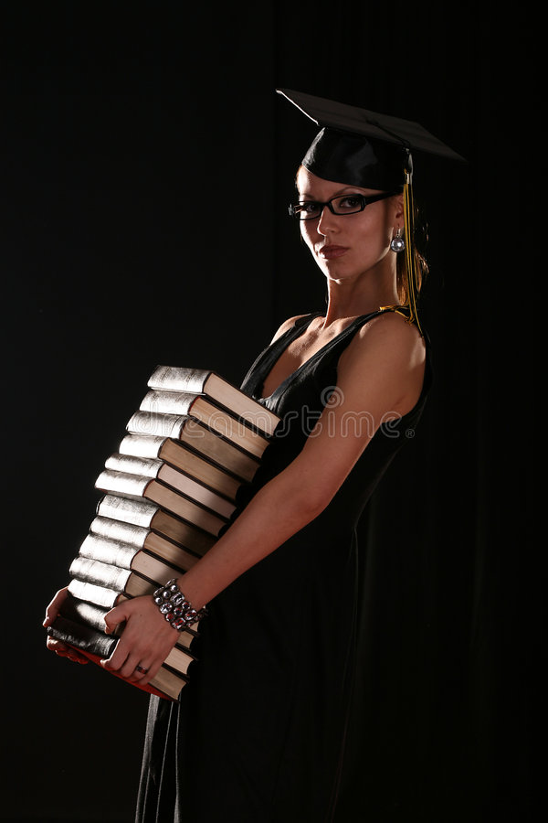 School girl. With graduation hat holding pile of books, isolated on black royalty free stock photo