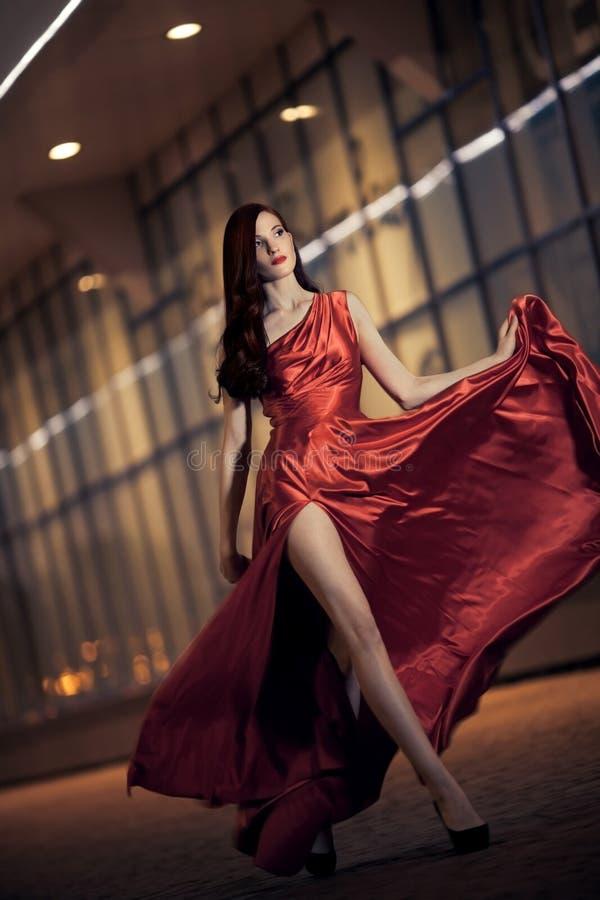 Sexy schoonheidsvrouw in fladderende rode kleding royalty-vrije stock fotografie