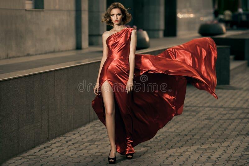 Sexy schoonheidsvrouw in fladderende rode kleding royalty-vrije stock afbeeldingen