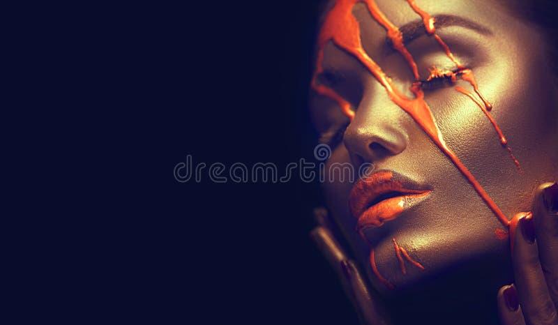 Sexy schoonheidsvrouw met gouden metaalhuid De gouden verf bevlekt druppels van het gezicht en sexy lippen royalty-vrije stock fotografie