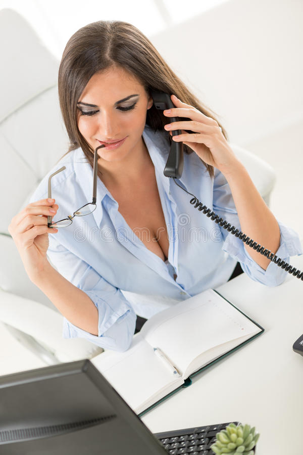 Secretary With Cleavage. A young pretty businesswoman with cleavage sitting at a table in front of the computer and planner. While phoning, holding glasses in royalty free stock photography