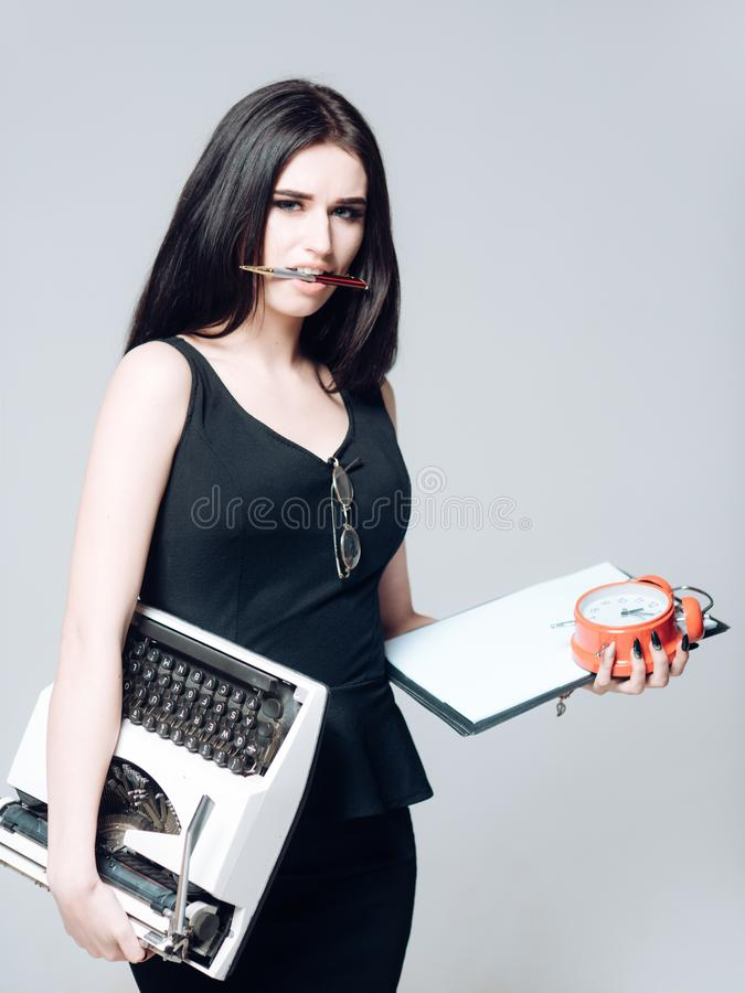 secretary with clipboard, clock and typewriter in her hands. Busy lady holding pen in her mouth isolated on gray stock photo