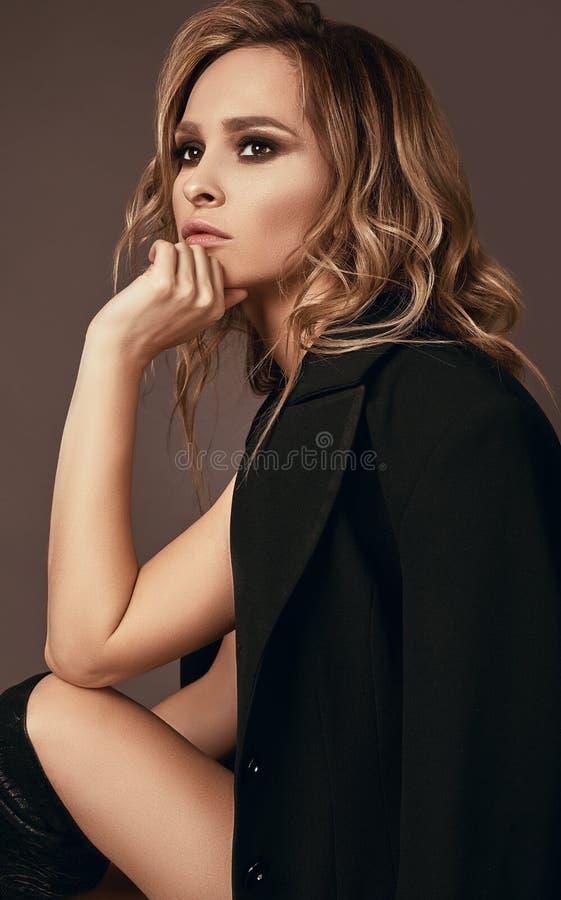 seductive blonde girl in underwear and black coat stock photos