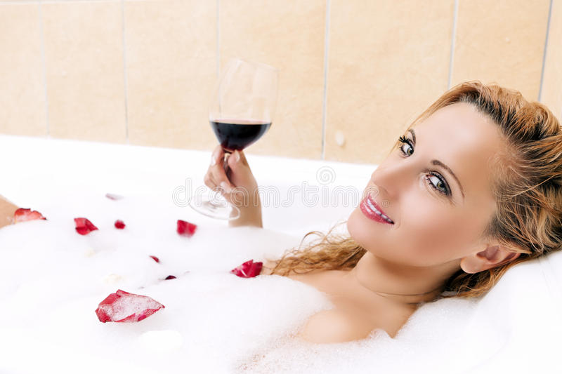 And Sensual Blond Female Relaxing in Foamy Bath. Covered with Rose Petals.Drinking Red Wine from Glass. Horizontal Image stock photo