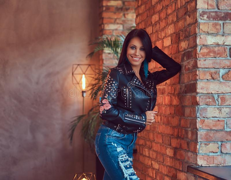 sensual brunette posing in stylish leather jacket and jeans leaning against a brick wall. stock photo
