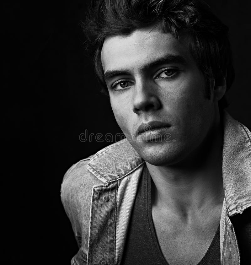 Serious male model posing in blue jacket on dark shadow bac. Kground. Fashion style contrast vogue portrait. Black and white royalty free stock image