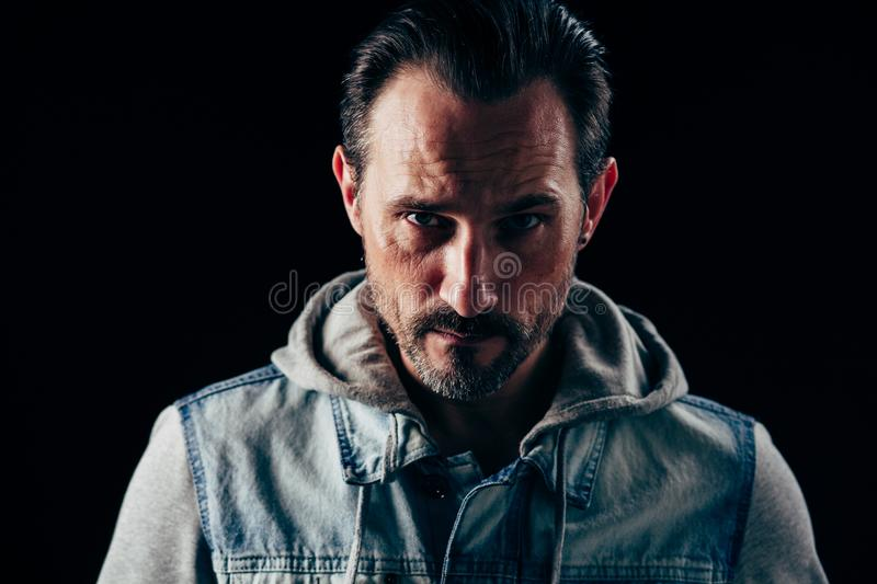 Serious strong man. Dark haired and beardy handsome man with serious look stock photography