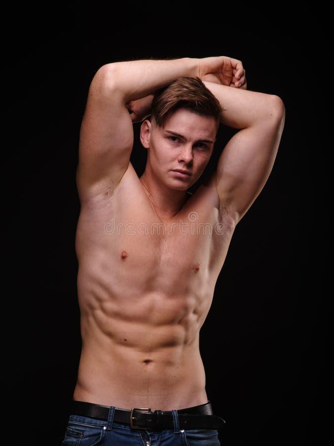 Sexy, shirtless, expressieve jonge mens op een zwarte achtergrond Training, opleiding, sportenconcept stock afbeeldingen