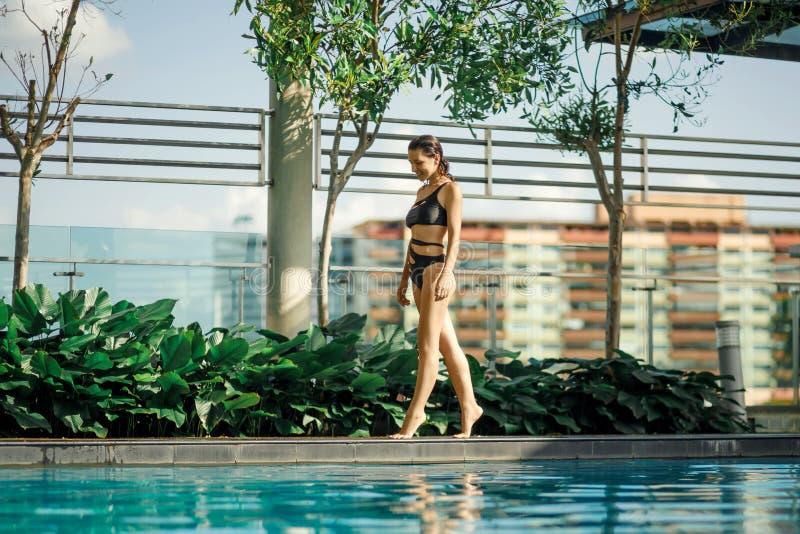 Sexy slank Kaukasisch brunette die tussen groene struiken en bomen op rand van zwembad op dak met cityscape lopen royalty-vrije stock afbeeldingen
