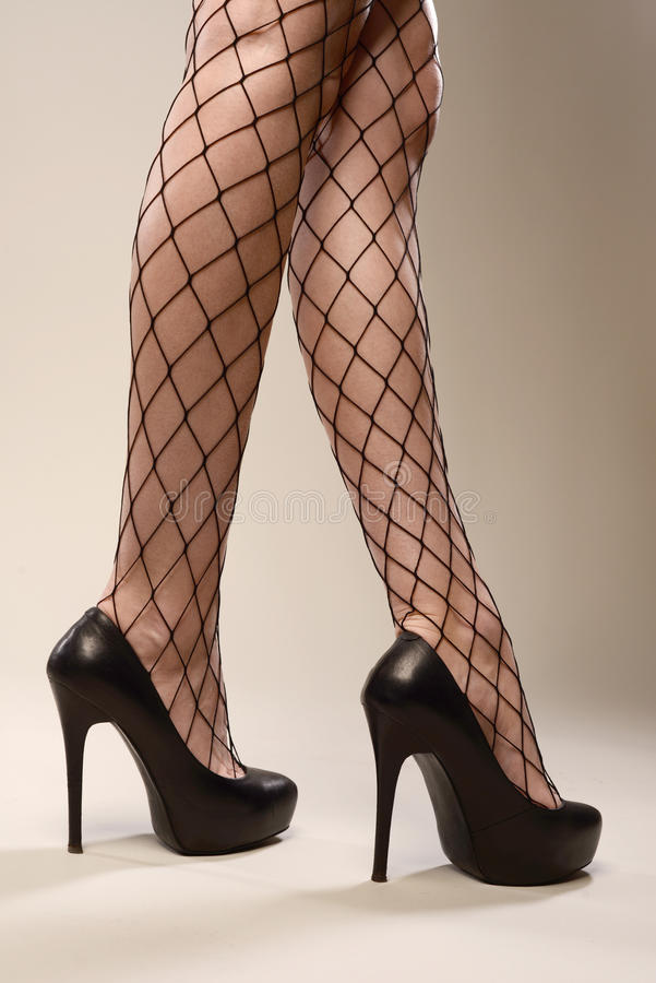 Sexy slanke mooie benen in zwarte netto legging en hoge hielenschoenen stock foto