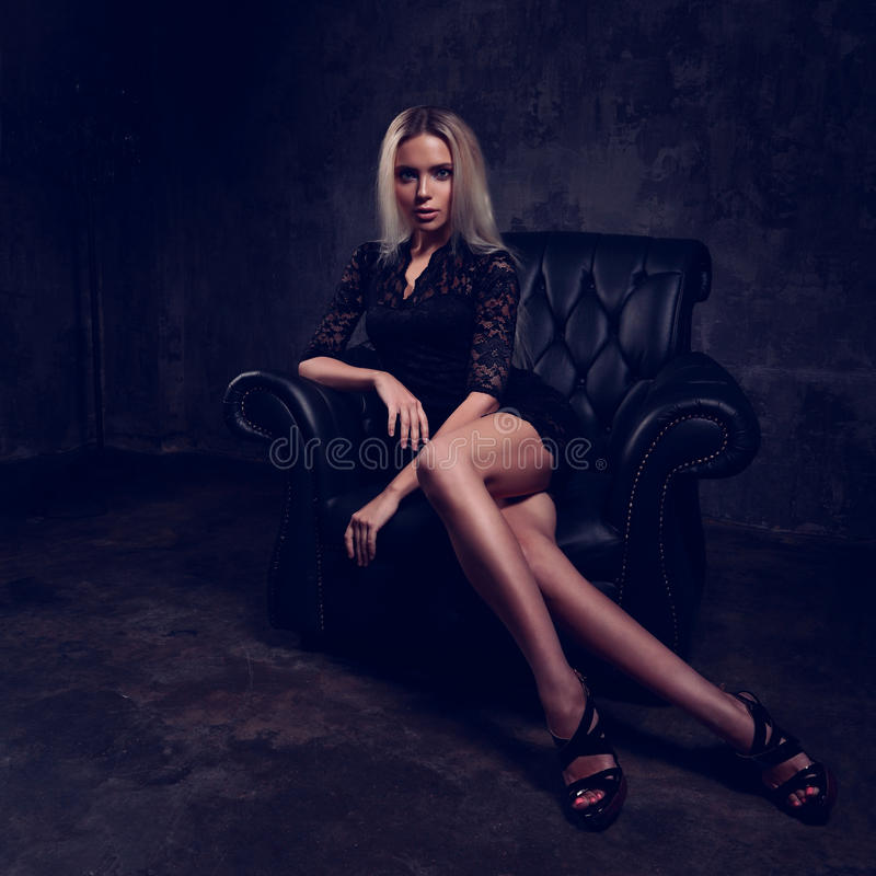 slim blond model sitting in fashion armchair in black dress stock photo