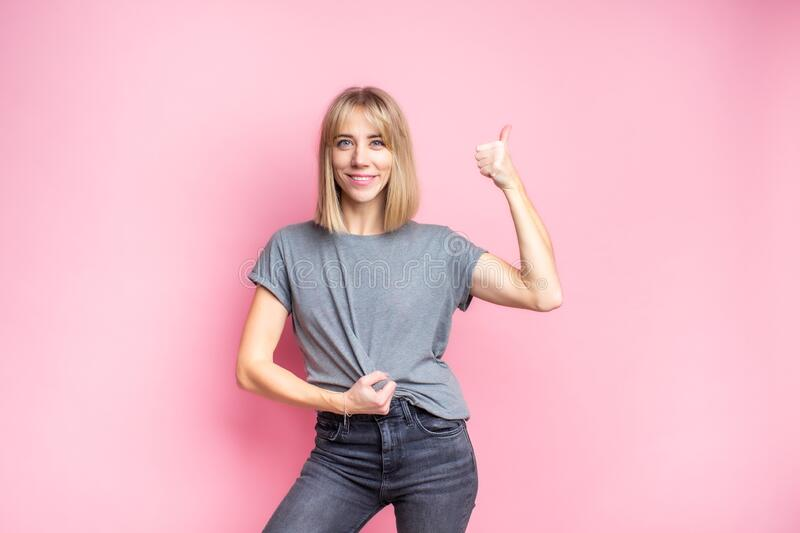 Sexy slim blonde woman in grey t-shirt and dark jeans posing on a pink studio background and showing thumbs up. Copyspace.  stock photos
