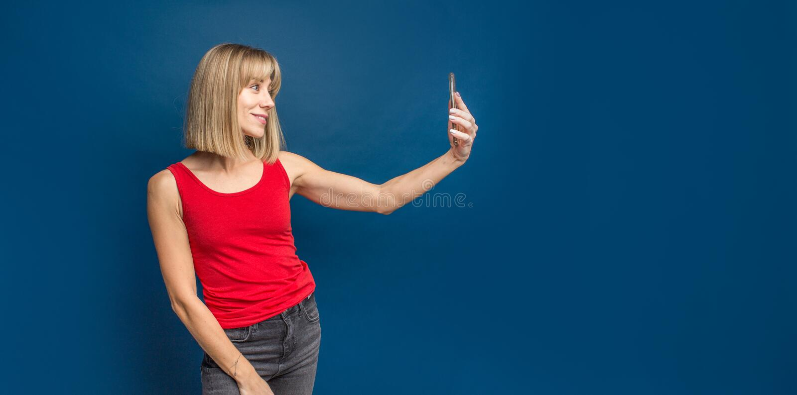 Sexy slim blonde womanin red t-shirt on a blue studio background making selfie with smartphone. Copyspace.  stock photography