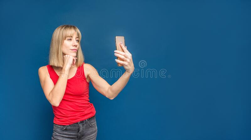 Sexy slim blonde womanin red t-shirt on a blue studio background making selfie with smartphone. Copyspace.  stock images
