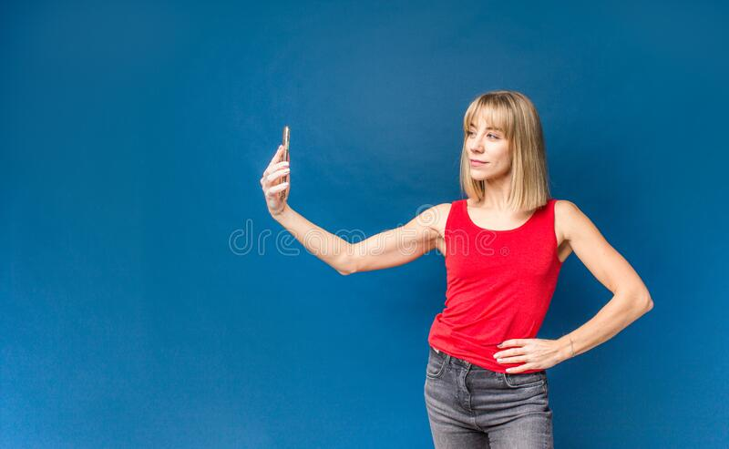 Sexy slim blonde womanin red t-shirt on a blue studio background making selfie with smartphone. Copyspace.  royalty free stock image