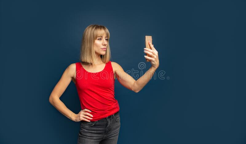 Sexy slim blonde womanin red t-shirt on a blue studio background making selfie with smartphone. Copyspace stock image