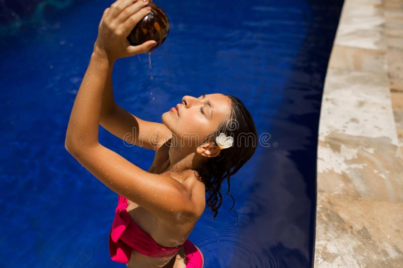 slim brunette young female watering herself with fresh coconut milk in pool with crystal blue water. Royal tropical resort royalty free stock photo