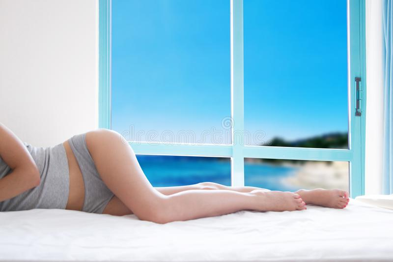 Sexy slim female body on bed in tropical hotel, Bahamas Carribean vacation concept stock images