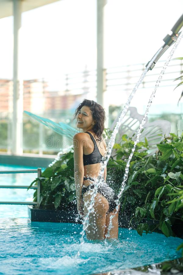 Sexy slim female in swimsuit takes shower in swimming pool between green bushes on rooftop with city scape background royalty free stock image