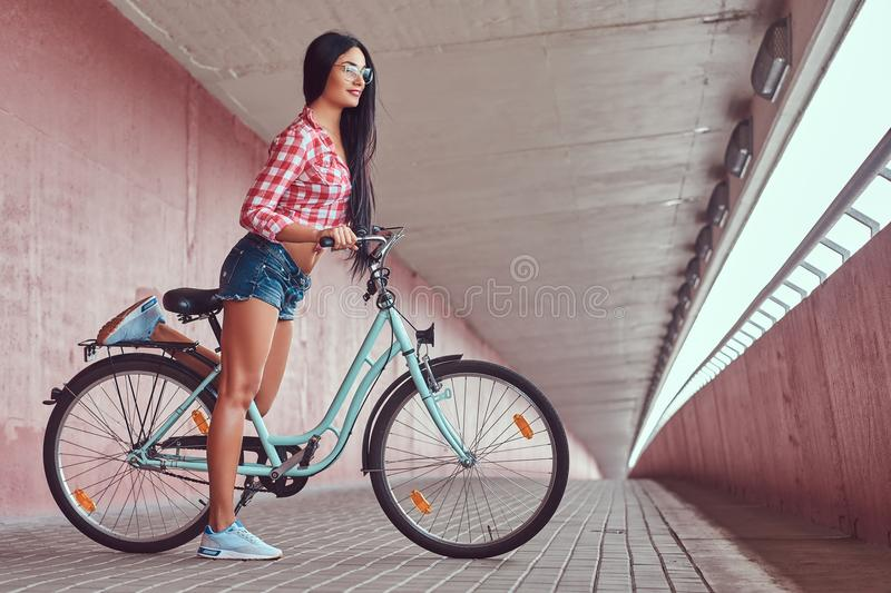 stylish brunette girl wearing a pink flannel shirt and denim shorts in glasses, posing with city bike against a royalty free stock photo