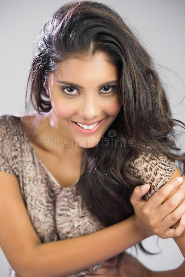 smiling brunette looking at camera touching her shoulder stock photos