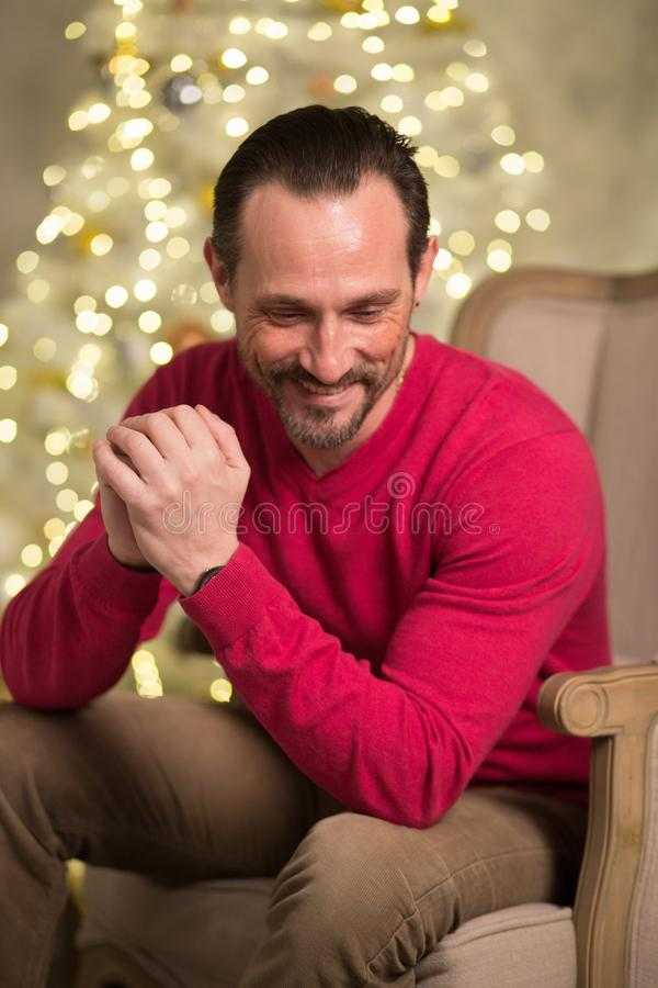 Handsome man in arm chair. Smiling men in red sweater. Sitting in arm chair royalty free stock photos