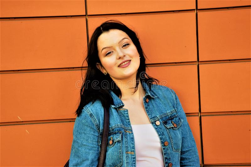 smiling woman on the background of a red wall royalty free stock photo