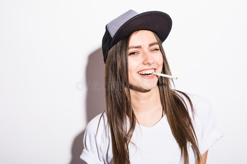 Smoking beautiful woman in cap with cigar closeup studio shot. Smoking beautiful woman cigar closeup studio shot royalty free stock photography