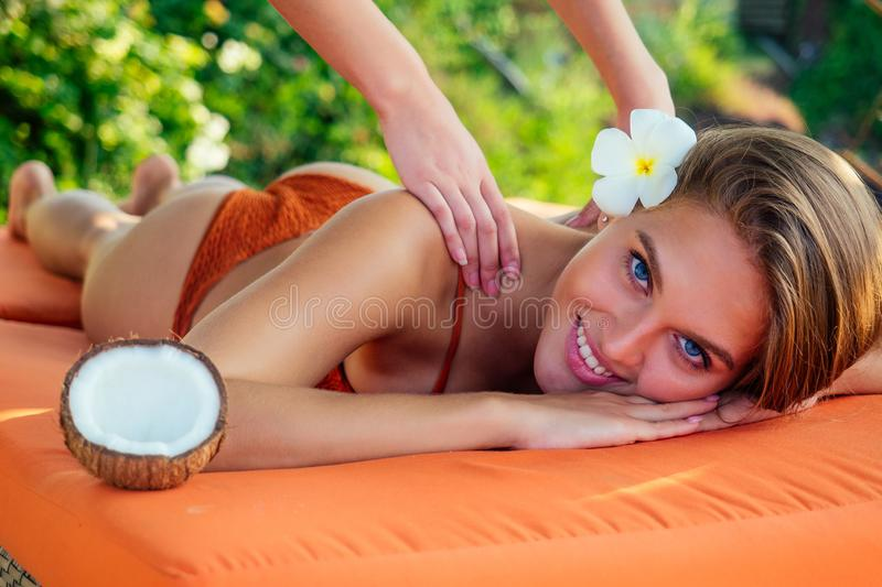 Sexy snow-white smile,perfect skin woman plumeria flower relaxing massage on beach.girl pampering in the Thai spa salon royalty free stock photo