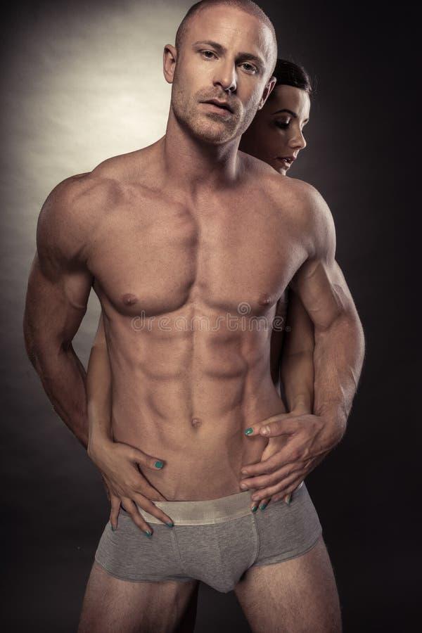Sexy spier naakte mens en vrouwelijke handen stock fotografie