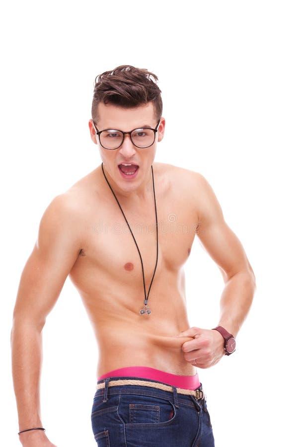 Sexy spiermens controleert die hoe pasvorm is hij stock foto