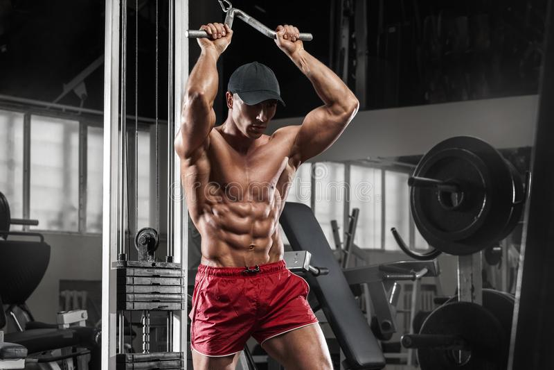 Sexy spiermens die in gymnastiek uitwerken die oefeningen, sterke mannelijke naakte torsoabs doen stock foto's