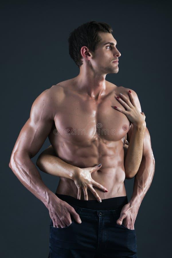 Sexy spiermens en vrouwelijke handen die zijn borst houden stock afbeelding