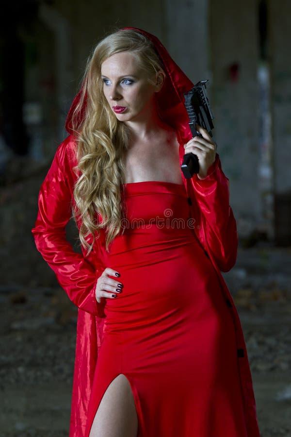 Sexy Spion im roten Kleid und im Mantel stockfotos