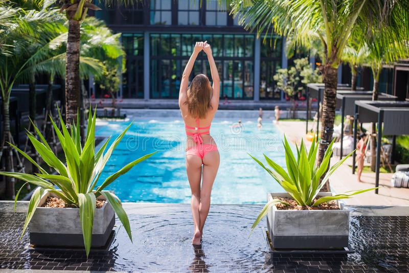 Sporty tanned back of young blonde woman in bikini posing on luxury pool on tropic island vacation.  royalty free stock image