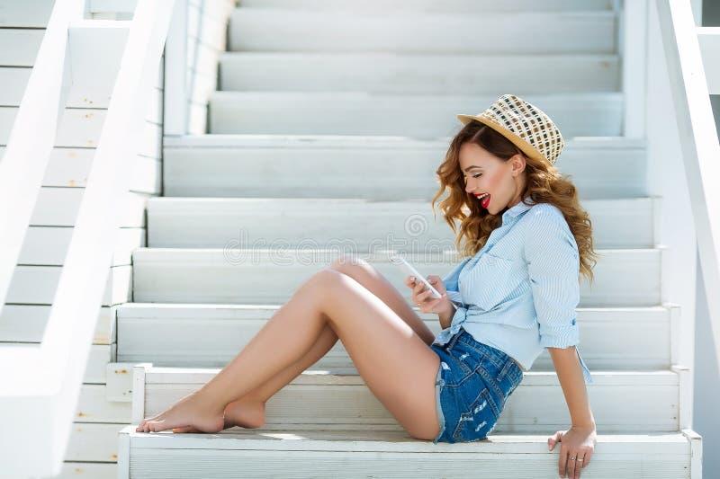 Sexy stilvolles Mädchen auf der Sommerterrasse nahe dem Meer, in den kurzen Denimkurzen hosen und in einem Hemd Mit Make-up und F lizenzfreie stockfotos