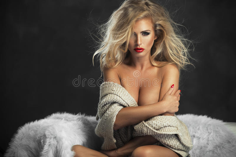 Strict woman with red lips. Sitting on couch