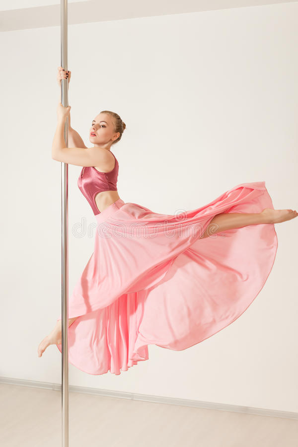 strip dancer exercising with pole in studio royalty free stock images