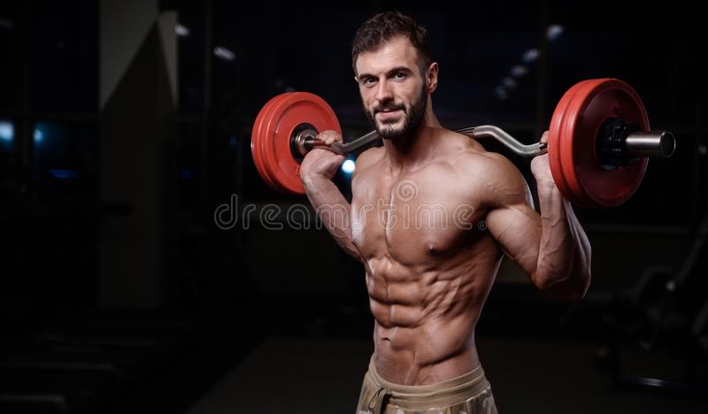 strong bodybuilder athletic men pumping up muscles with dum royalty free stock images